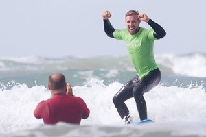 a man happy for his beginner surfboard surfing lesson