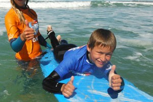 kid on surfboard as he learn to surf in Adelaide with coach